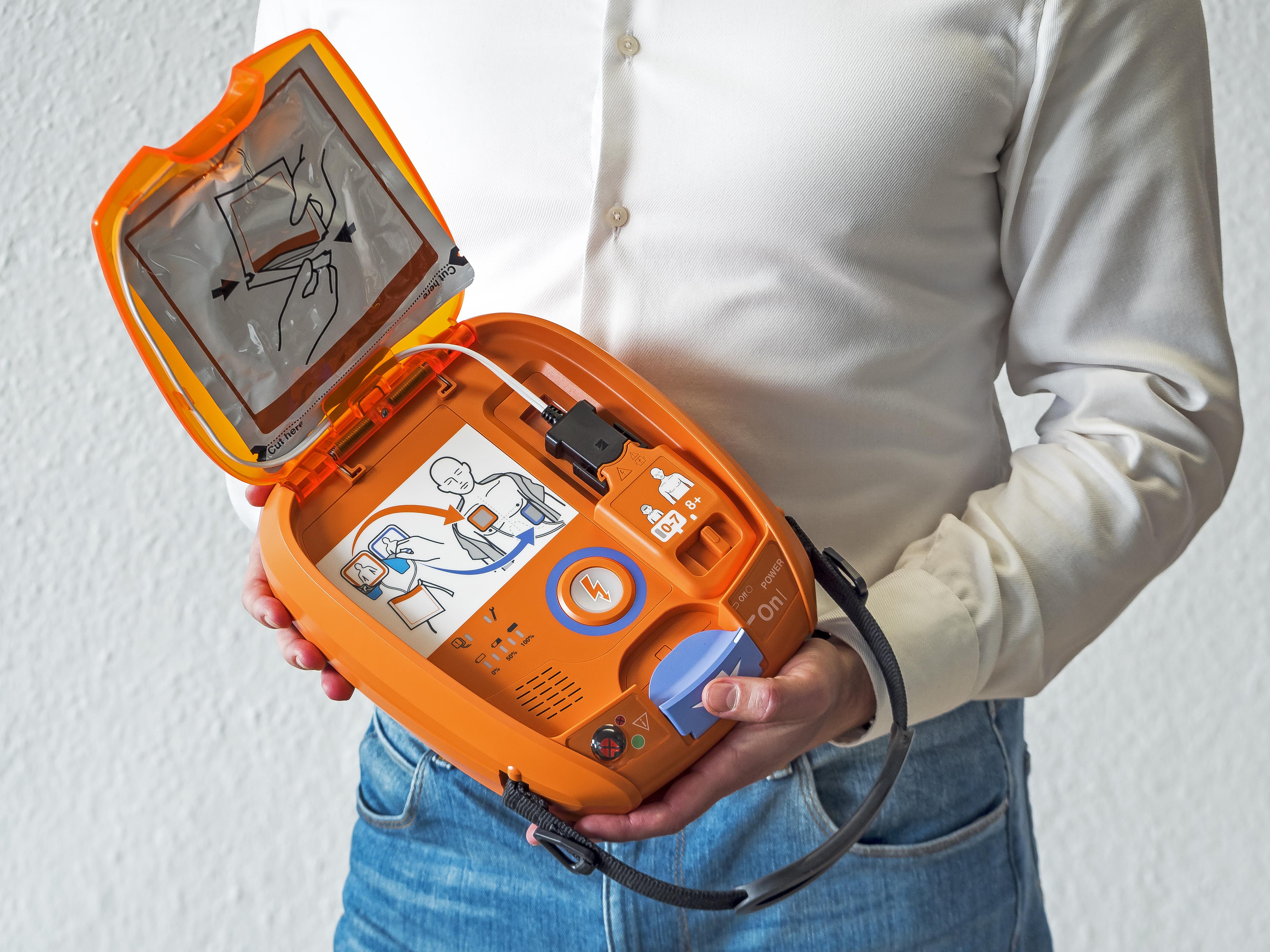 Mitarbeiter mit einem NIHON KOHDEN AED 3100 Defibrillator in der Hand