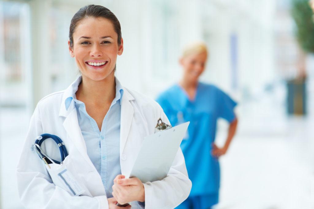 Ärztin und Arzthelferin lächeln in die Kamera