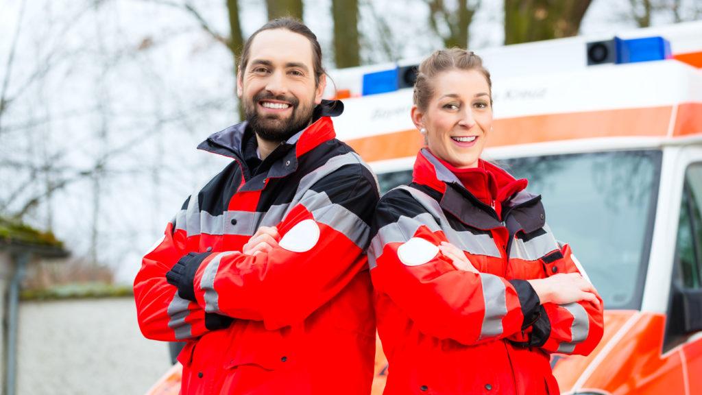 Zwei Rettungssanitäter vor einem Rettungswagen